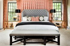 Amazing coral & gray bedroom with coral chevron pattern curtains window panels, gray wingback tufted bed, coral chevron pillow, white & gray fretwork pillows, charcoal gray throw, gray linen bench with silver nailhead trim and alabaster lamps with black shades.