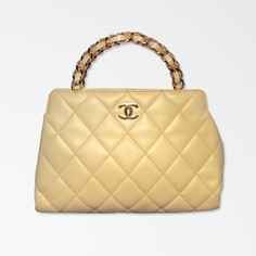 This beautiful Chanel handbag features a quilted, off-white leather exterior trimmed with gold hardware and one slit pocket along the back.