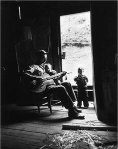 Eliot Elisofon | A Father Singing to His Children, Leslie County, Kentucky 1949 | sing | kids | music | guitar | the blues | barn | entertain | black & white photography | parenting | lullaby | 1940's | vintage | soul