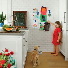 The kitchen sparkles with white subway tile and built-in cabinetry, including integrated fridge, which makes the space feel larger. A classic apron sink with gooseneck faucet provide ample room for doing dishes. Coastalliving.com