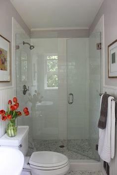 Inspiration for basement bathroom remodel. Love the glass shower door, paneled walls, and marble mini-hexagons floor tile