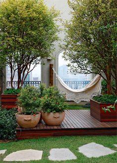 As jabuticabeiras, árvores mais altas do jardim, foram plantadas em caixas para se desenvolverem melhor. o deque unifica o visual deste canto, que tem ainda minirromãs em vasos de cerâmica. Para dispor a rede, toras de eucalipto