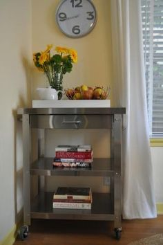The wheeled Danver stainless steel professional kitchen cart featuring two shelves; a front drawer and a side towel bar and hooks for utensils replaced an old-style butcher block cart.