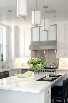 Peter Pennoyer Architects: White kitchen with crisp white kitchen cabinets paired with marble slab countertop and ...