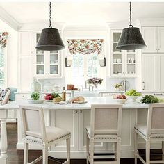 Light Atlanta Kitchen | To create an elegant, light-filled look, Suzanne painted the walls and cabinetry the same creamy white and then continued the less-is-more palette with white marble countertops, a white tile backsplash, and linen barstools. | SouthernLiving.com