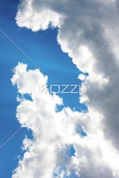 sunrays through clouds - Sun rays shine through a cloud with a bright blue sky
