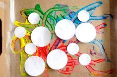 Place white circles on finger paint designs.