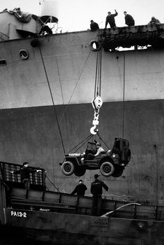 Lower Away. Down goes a jeep from the deck of a Coast Guard-manned assault transport into a landing craft, during amphibious maneuvers of Coast Guard and infantry units in the European war theatre.