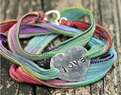 """This Rainbow Ribbon Wrap Bracelet is sure to brighten your spirits on a rainy day. All you need to create this elegant, effortless bracelet is multicolored ribbon and a silver charm. Choose a charm that represents you, or, if you've been making jewelry for a while, design your own. You can stamp a meaningful message like """"LOVE"""" or """"SMILE"""" onto a stamping blank for a personal touch."""