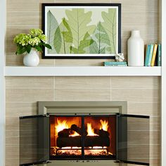 Porcelain tile (#486466) laid in a stacked pattern adds sleek lines to the surround. Extending the tile to the ceiling creates height and draws the eye. Much as you'd update hardware, a new fireplace door (#358248) delivers an on-trend finish and cleaner lines to the masonry fireplace. A sturdy, streamlined mantel face extends from wall to wall.