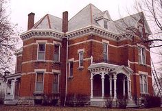 Old house, located in Fayette, Missouri, a small town in the central part of the state. The house has Gothic, Queen Anne, and Italianate designs and influences. It dates from the late 1870's to early 1880's. A simple yet striking brick creation with millwork ornamentation not overbearing. The house still looks impressive, despite the fact that it has seen some pretty lean years of minimal upkeep and some neglect. Currently, it appears to be undergoing a major renovation, as the opposite side from this view is stripped and covered with scaffolding and ladders. The house has a polychrome slate roof (very faded and hard to see in this photo, which was taken on an overcast  November day), as well as a stone foundation and stone window lintels.