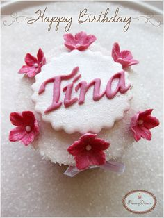 Birthday cupcake with name decorated with handmade pink flowers.