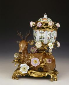 Ormolu-mounted porcelain pot-pourri vase, mid-18th Century, comprising a Chinese porcelain stag on a European ormolu rococo base, both mid-18th Century, one branch supporting an ormolu-mounted late-17th Century Chinese Kakiemon bowl and lid, converted from a teapot, the knob Japanese, all mounted with brightly coloured Vincennes porcelain flowers.