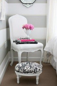Love the gray & white striped walls and the gorgeous white chair with a dash of pink and most importantly the CHANEL BOOK staged with it all!