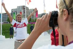 TEAM CANADA KEEPS THEIR ENERGY HIGH! Swimmer Blake Worsley has his photo taken by swimming teammate Stephanie Horner during the team welcome ceremony at the Olympic Village July 25, 2012.