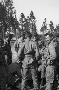 Dick Winters (facing the camera in the back) teaching his soldiers to pack their parachutes. Skip Muck is the man on the right looking at the camera.