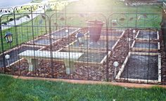 """The tip is to design the garden to be a real showstopper, with pretty solar lights, urn centerpiece, and a bench. But what I see is a perfect garden for a back yard that has """"gone to the dogs"""" - let them romp around the outside of it while your veggies grow undisturbed."""