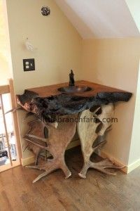 Live edge old growth redwood burl and real moose antler sheds and copper sink with pump style faucet complete this rustic vanity