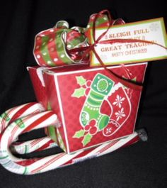 "CANDY CANE SLEIGH-We've taken a Christmas Chinese take-out box, added candy canes on the bottom to make it look like a sleigh... It is ADORABLE!! The tag reads, ""A candy cane sled has come a-gliding, Carrying sweet wishes and lots of good tidings! Merry Christmas Teacher"" or ""A sleigh-full of goodies for a great teacher! Merry Christmas"""