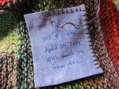 Label made from a cloth napkin, written in ink and whipstitched onto a knit blanket