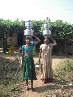 Two Indian women performing the typical daily task of bringing water to their family from the village pump.