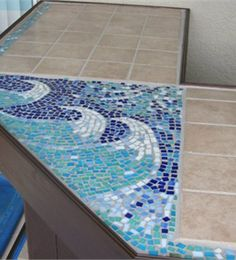 An elaborate L-shaped bar made of plywood, T-11, and a full tile top with intricate ocean waves mosaic.