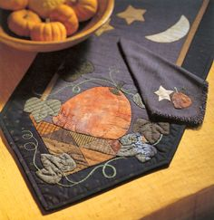 Pretty appliqued pumpkin table runner with coordinating napkins by designer Linda Johnson.