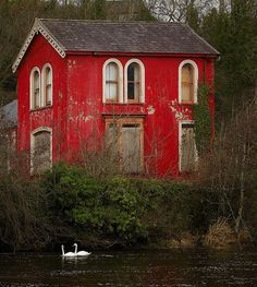 Well worn red home on a river in France.