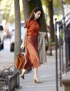 Amal Clooney and Katie Holmes are both fans of burnt orange outfits for fall, proving it's the color trend of the season.
