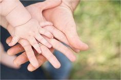 Cute family portrait - everyone's hands piled up, displaying the littlest hand at the top.