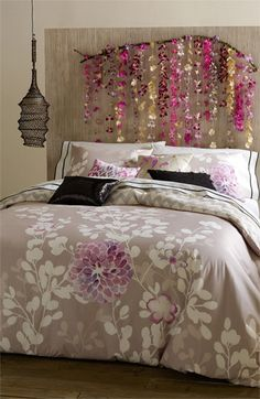 DIY Headboard. Find an interesting branch and mount it to the wall after hanging decorations from it. Love the colors. :-)