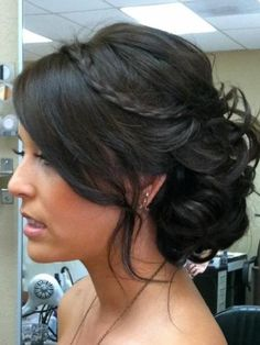 Fancy messy bun with bangs and small braid.