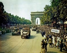 """On August 25, 1944, crowds of people line the Champs Elysees to watch the Allied soldiers ride into Paris through the Arc de Triomphe in tanks, half tracks and on and motorcycles. A large sign on the right side of the street reads, """"Vive de Gaulle."""" On the left, another reads, """"De Gaulle au pouvoir."""" French General Charles de Gaulle organized the """"Free French Forces"""" in England during World War II and later became President of France."""
