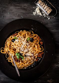 Pasta with Tomato Pesto, Italian Sausage, Black Olives, Basil and Pine Nuts.