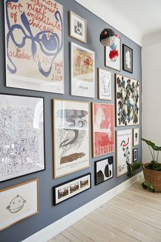 Cool art wall with both posters and prints and personal Japanese souvenirs to break the lines. All on a backdrop of a dark blue wall.