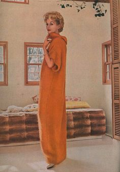 Lisa Fonssagrives in an at-home sheath in orange mohair, loosely sleeved, with an un-clutching turtle neck. Designed and worn by Lisa in her own work room.    Photographed by Frances McLaughlin-Gill for Vogue, December 1958.