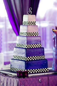 Black and white racing checks trim each tier of this five tier fondant cake for this racing themed wedding.  Photo by Chrissy Lambert Photography.