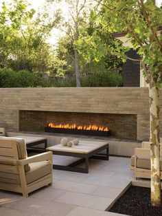 Andrea Cochran's propensity for clean lines, geometric balance, and subtle colors is on display in this garden at a residence in Atherton, California, including a large stone fireplace that forms an essential part of an outdoor living room. patio, backyard, outdoor living rooms, outdoor fireplaces, fireplace wall, outdoor spaces, stone fireplaces, garden, fire pit