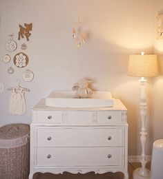 A charming grouping of artwork and trinkets beside the changing table #nursery