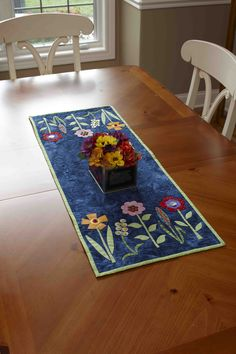 "Easy fused flowers and colorful buttons adorn this cute table runner. Quilt designed by Jodie Davis and is 14 1/2"" x 38 1/2""."