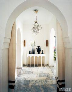 Bruno Frisoni's partner, Hervé Van der Straeten, designed the Cubist light fixture and arched console for the entrance hall.
