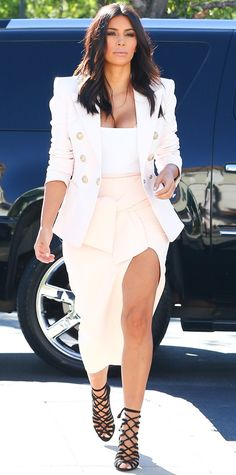 Kim Kardashian opted for a more demure look (by Kim Kardashian standards), pairing her white Alaia bodysuit with a sexy pink thigh-high slit Maticevski skirt and adding structure with a sharp white Balmain blazer. As for shoes, she upped the drama with black lace-up Hermes heels.