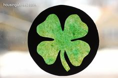 """Stained glass"" shamrock. Fun kid-friendly project using coffee filters, green and yellow water colors, black tempera paint, small medicine dropper, and free shamrock template."