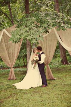 Burlap and tulle draping for an outdoor wedding...this would be very pretty adding lights and a bow for color...