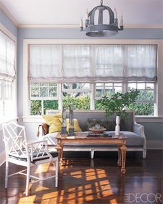At a weekend home in Southampton, New York, Emma Jane Pilkington decorated the sunroom with serene powder-blue walls and sheer window shades.