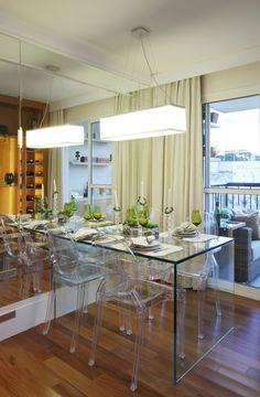 """A mesa em vidro e as cadeiras em acrílico incolor deixam a sala de jantar sofisticada e com um ar """"clean"""". Agregadas à parede revestida em espelho, parecem ampliar o ambiente http://ow.ly/blR6H"""