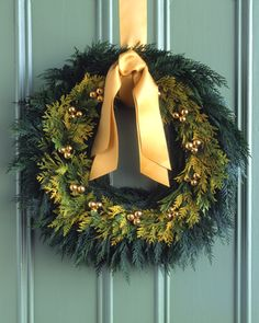 Golden-Cedar Wreath  Go for the gold and enrich a simple cedar wreath with tiny bells, sprigs of golden cedar, and a matching satin bow.