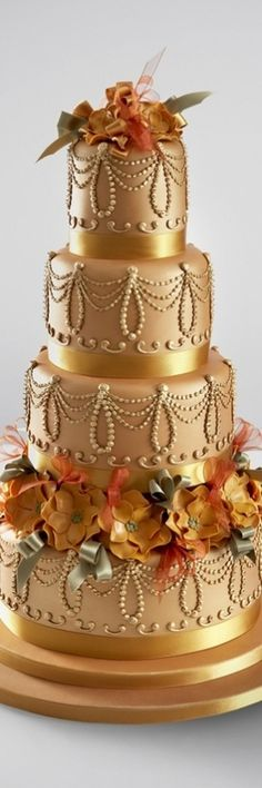 Vintage Gold wedding cake decorated with sugar flowers and ribbon loops. Inspired by the 1960's movie Hello Dolly.