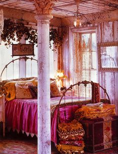 Bedroom decor with chippy paint, metal bed frame, net curtains, vines, and piled mixed-print textiles appeals to me, but the orange and fuchsia color scheme is a bit too bright and jarring.