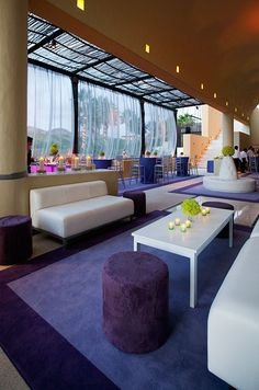 This modern lounge is enhanced with large purple area rugs, velvet pods, sleek white couches and lime green votives.